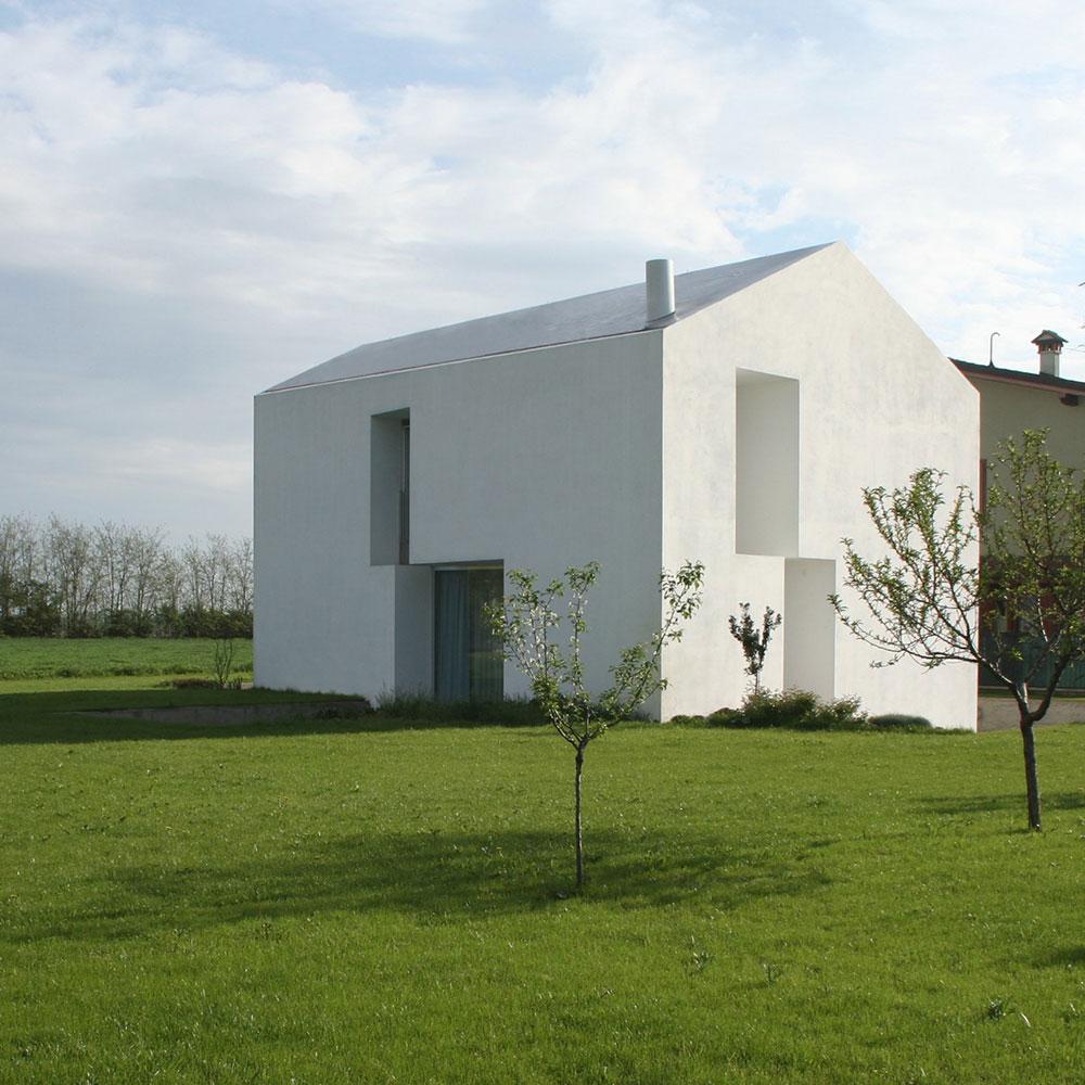 Abitazione completamente bianca collocata su un prato dietro un'altra casa