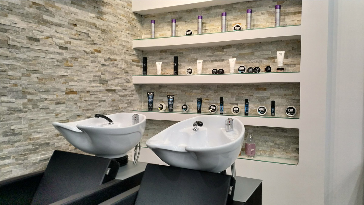 Due lavabi con dietro una credenza a muro con dei prodotti per capelli