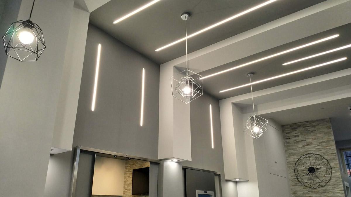 tre lampadari appesi al soffitto e luci lungo le pareti