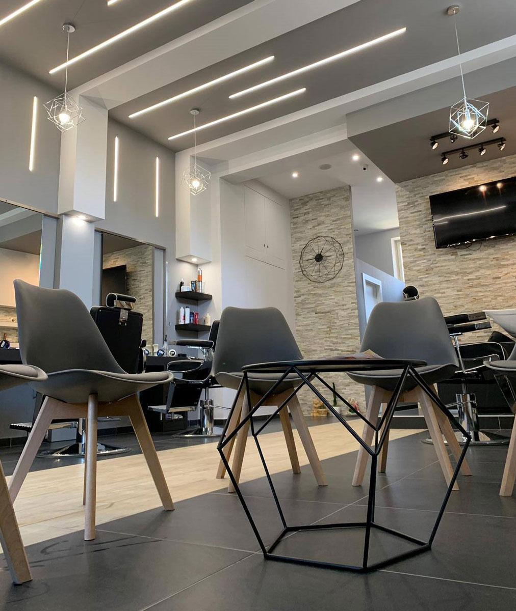 Tavolino in metallo di forma geometrica con attorno delle sedie grigie