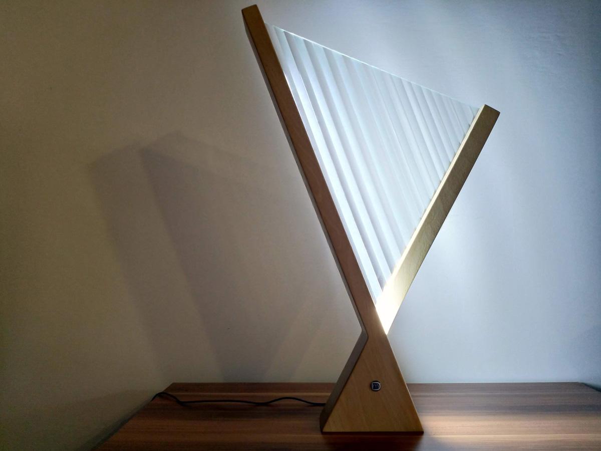 Lampada a forma di arpa vista frontalmente e appoggiata su un ripiano di legno