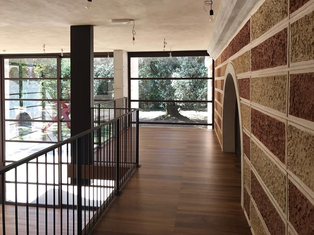 Soppalco in legno che segue un muro in mattoni rossi e bianchi e termina angolarmente con un'ampia vetrata