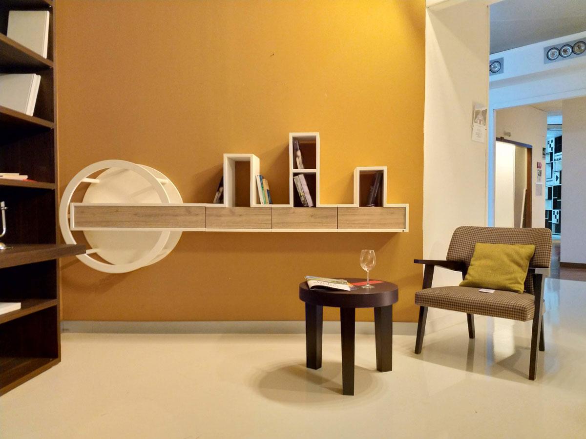 Stanza arredata con un poltroncina in legno, un tavolino a tre gambe e una mensola a muro in legno