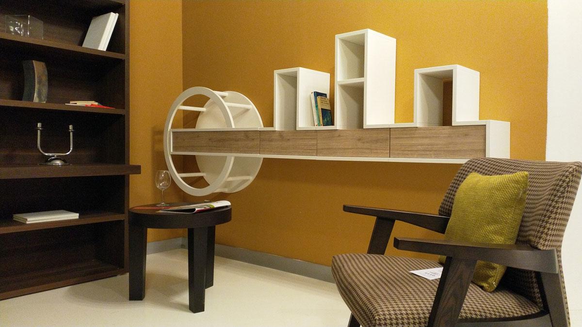 Stanza arredata con un poltroncina in legno, un tavolino a tre gambe, una mensola a muro in legno e una libreria nera