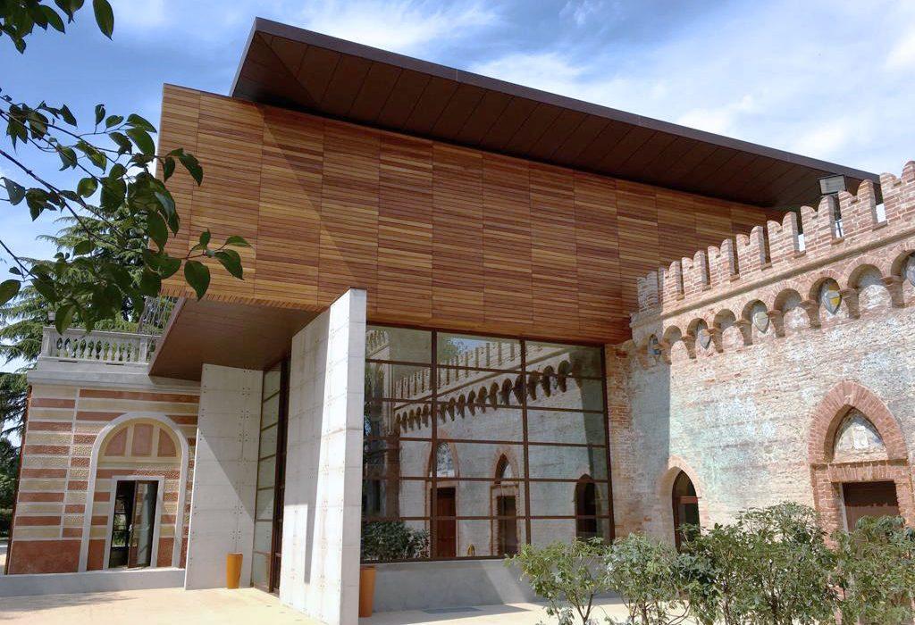 Esterno della Barchessa dove le vecchie mura in mattoni si intersecano con la struttura moderna in legno e vetro