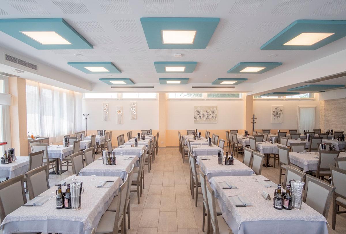 Sala ristorante con tavoli pronti e pannelli Phonolook sul soffitto