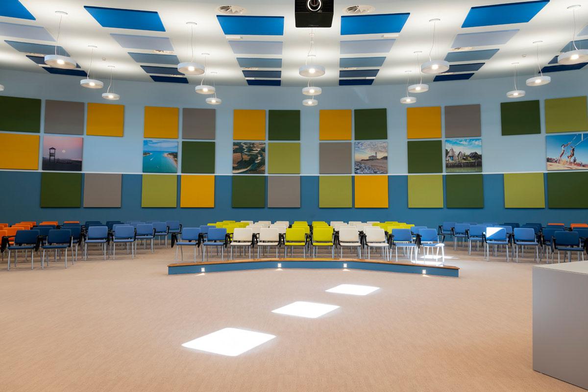 Auditorium con vari pannelli Phonolook di diversi colori appesi alla parete e al soffitto