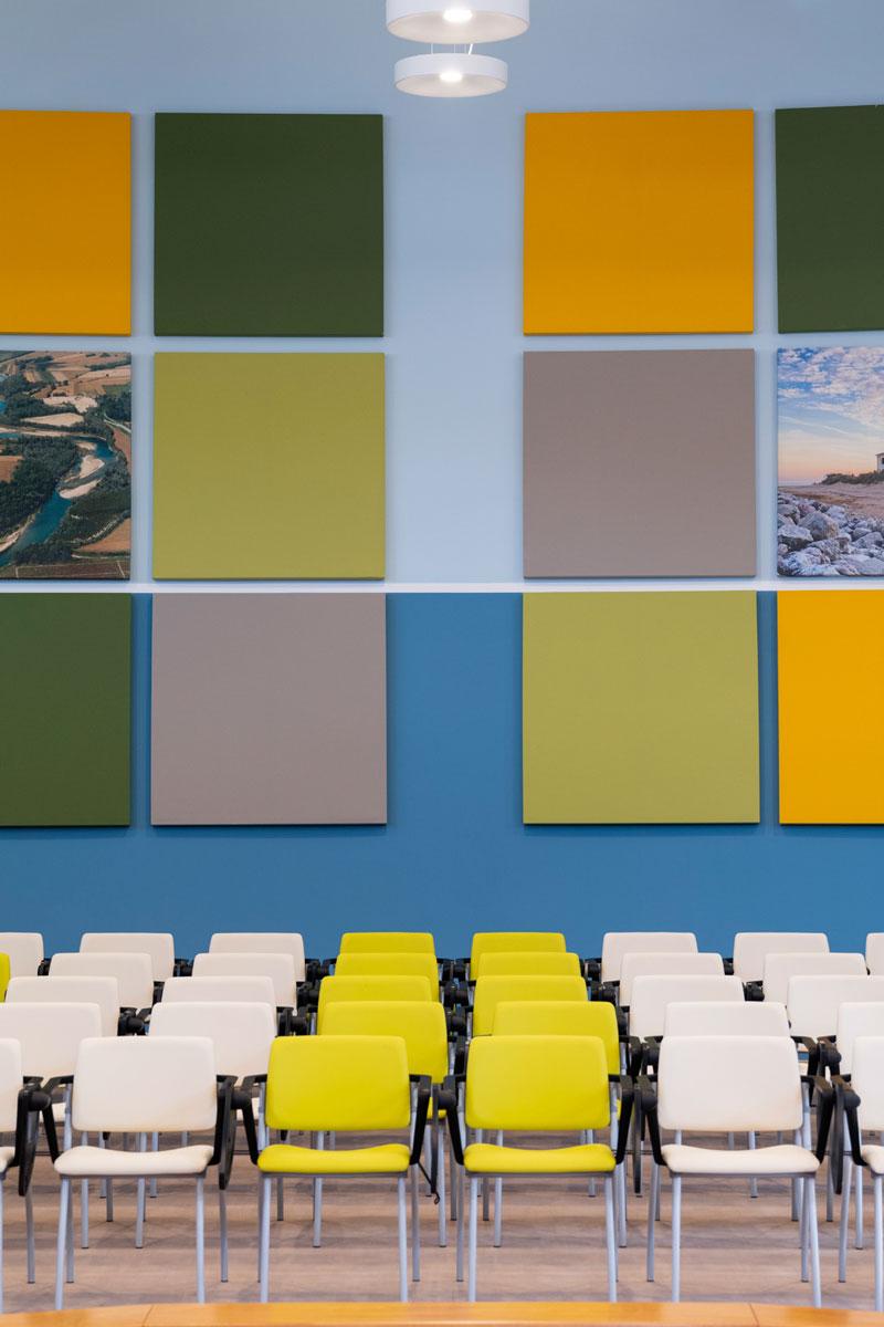 Sala conferenze con pannelli Phonolook appesi al muro di vari colori e stampe