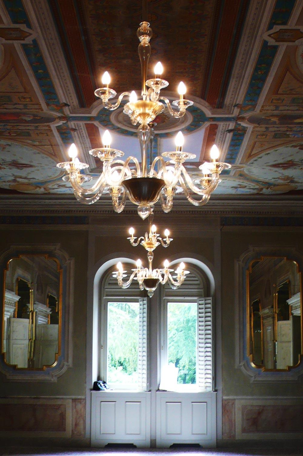 Due candelabri in fila appesi al soffitto all'interno di una stanza di una villa