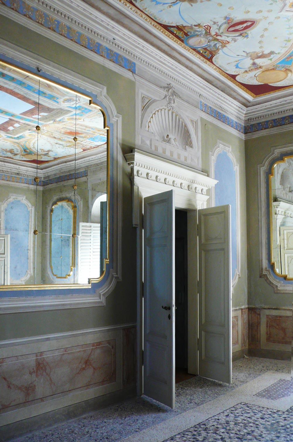 Stanza decorata di una villa con una porta bianca e a fianco uno specchio a muro