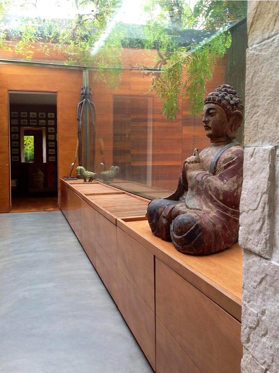 Statua di un Buddah su un corridoio in legno