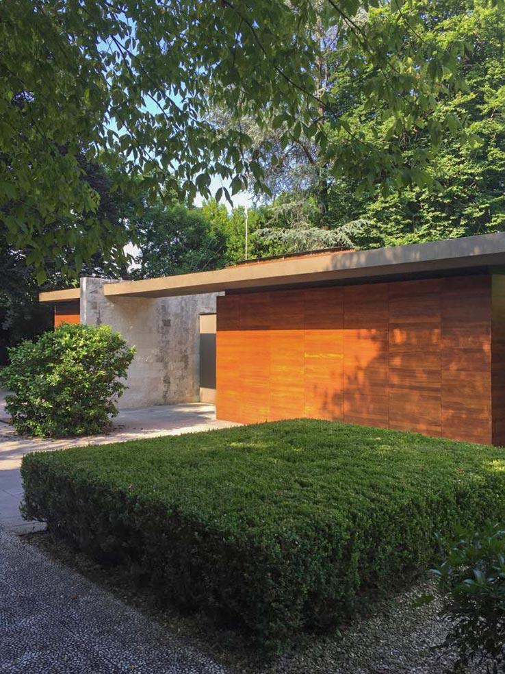 Siepe quadrata davanti ad un muro in legno