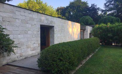 Facciata di un muro di mattoni bianchi che dà su un giardino