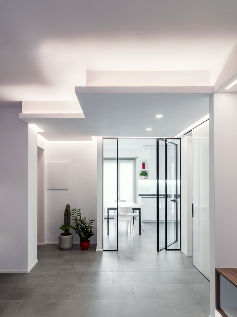 Room with ceiling lighting and behind a glass door a kitchen in the background