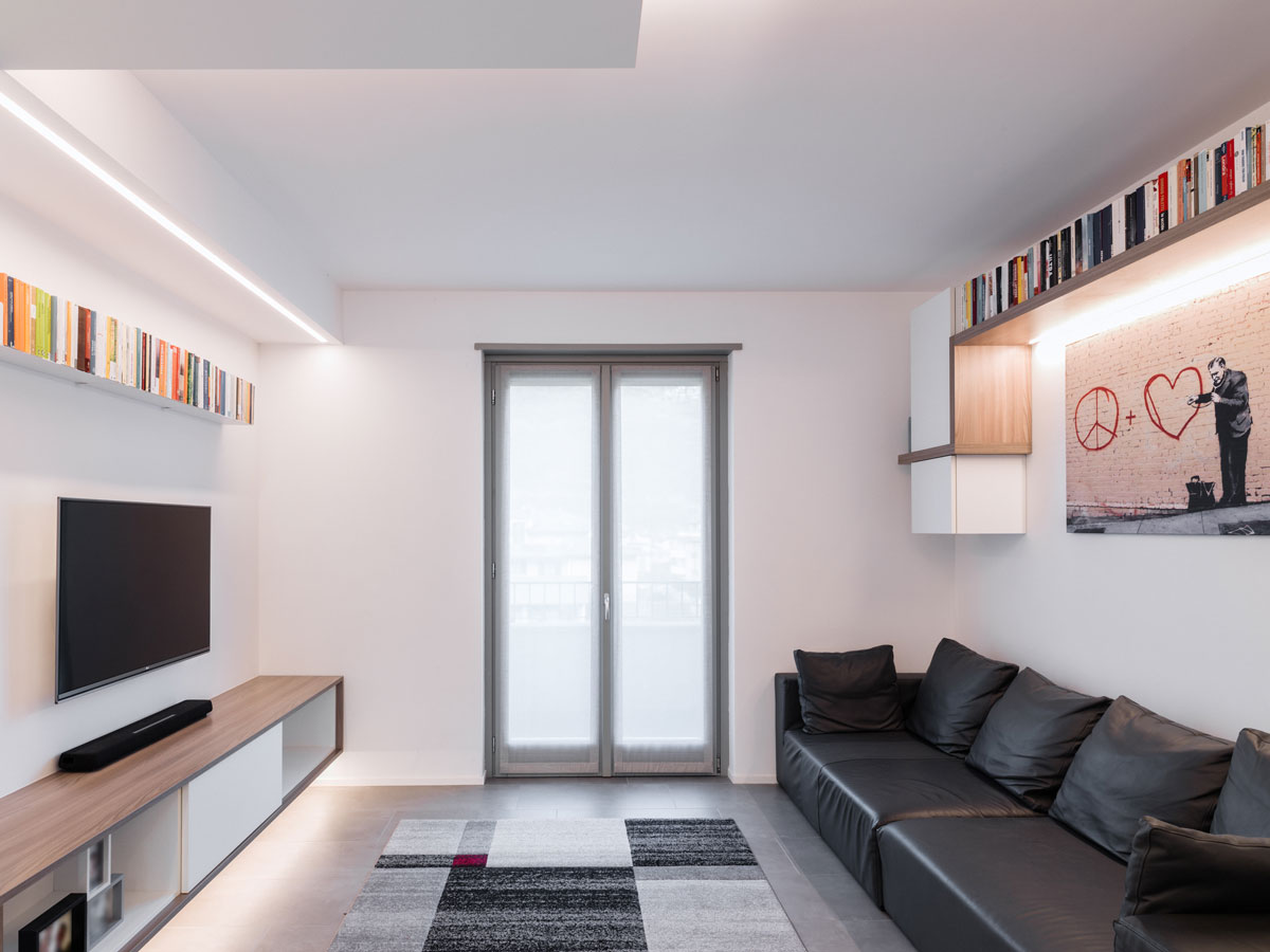 Living room with a black leather sofa on the right, a television on the left above a wooden cabinet and a central door