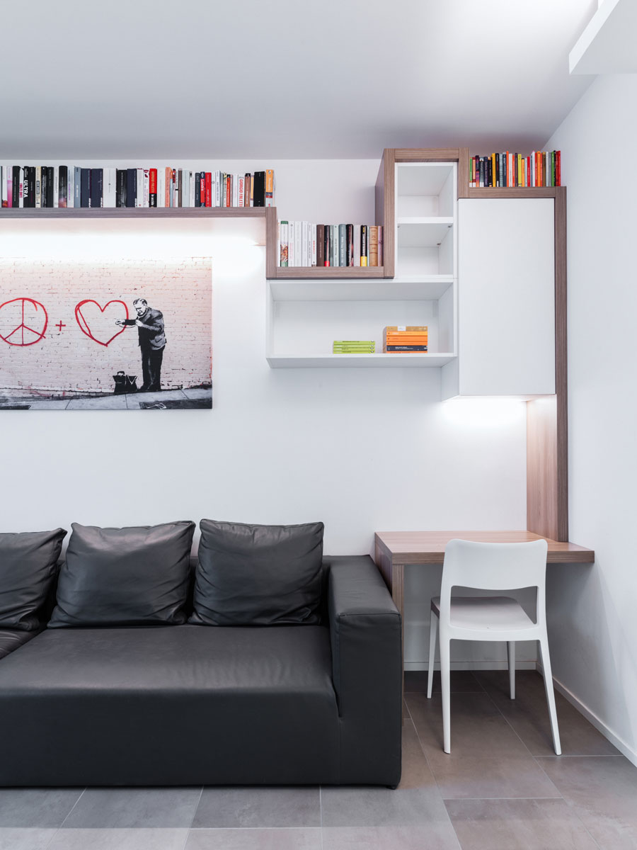 Study corner consisting of a black leather sofa and alongside a small wooden desk