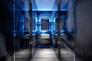 Corridoio con pavimento in legno e pareti in vetrata che portano ad uno specchio illuminato di blu