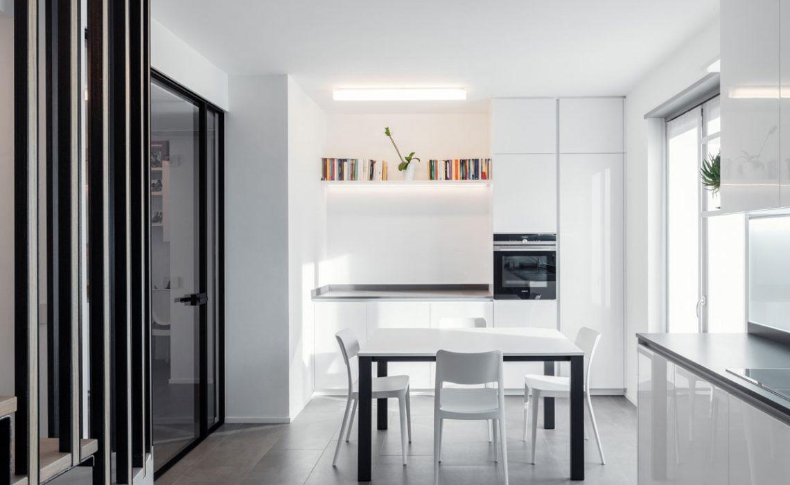 Cucina con al centro un tavolo con sedie bianche