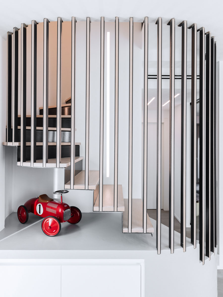 Suspended spiral staircase with a model of a red car nearby