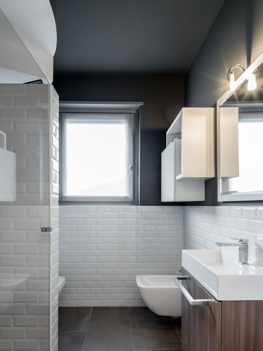 Bathroom with black walls and floors and white tiles and sanitary ware