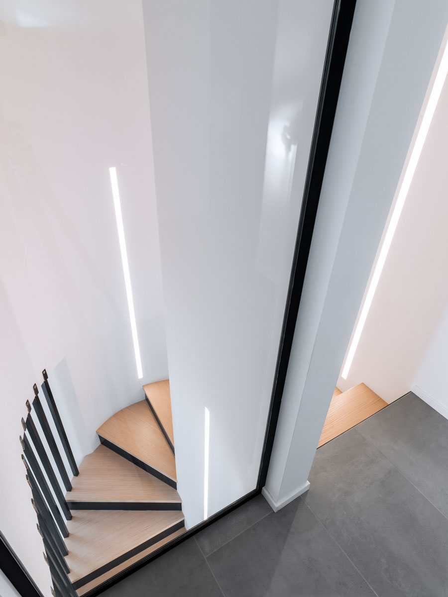 Column with a spiral staircase that descends into the living area