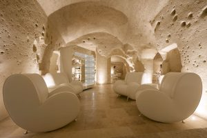 Esposizione di alcune poltrone e credenze bianche e pareti in pietra