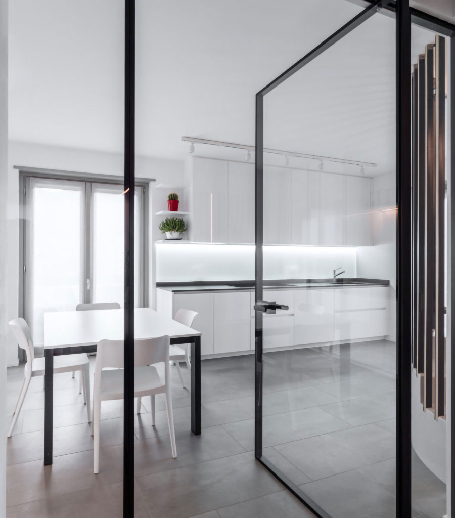 Glass door leading onto a kitchen with tables, chairs and white furniture