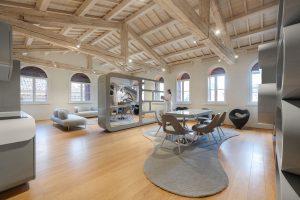 Open space con pavimento e soffitto in legno e arredamenti grigi