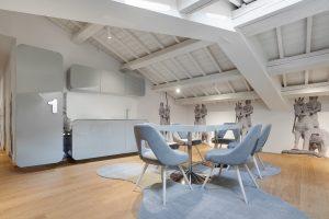 Open space con pavimento e soffitto in legno e tavolo e cucina di color grigio