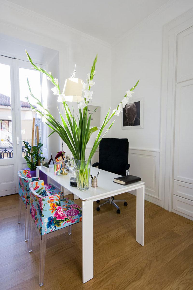 Studio con una scrivania bianca e un vaso di fiori poggiato sopra