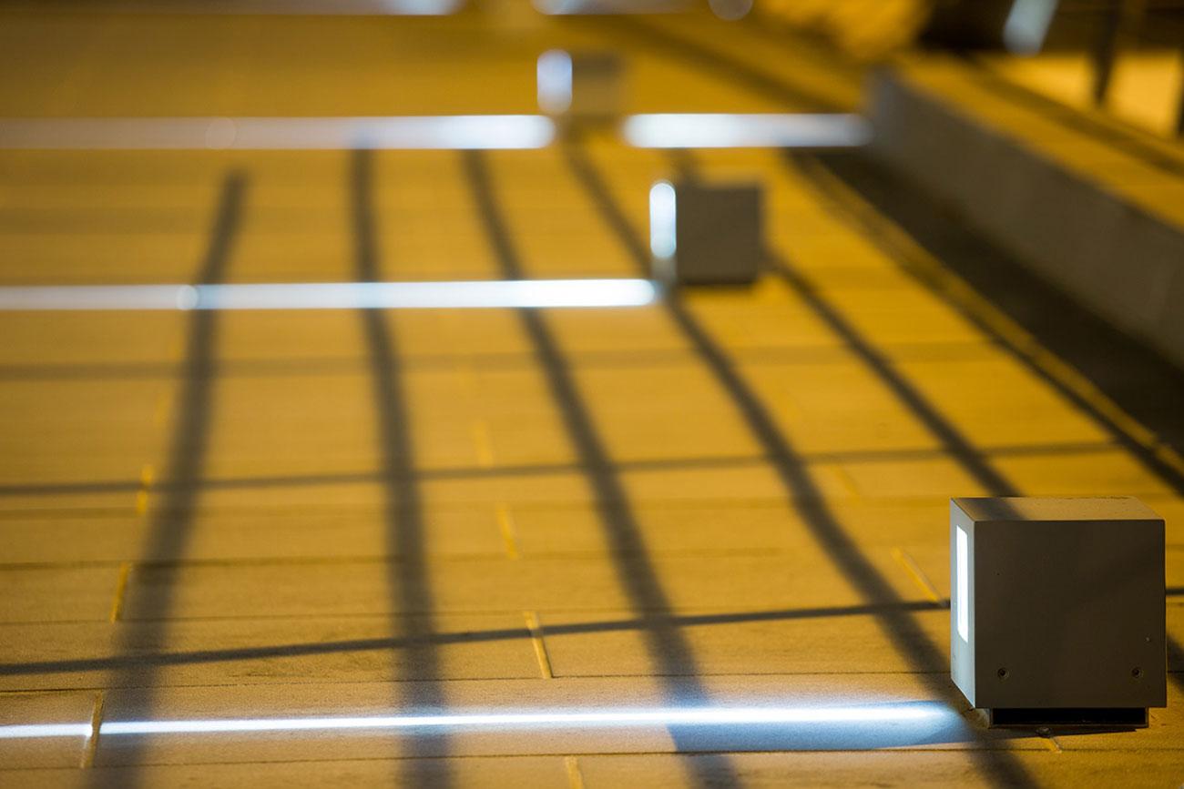 Quadrati metallici che proiettano un fascio luminoso sul pavimento in legno