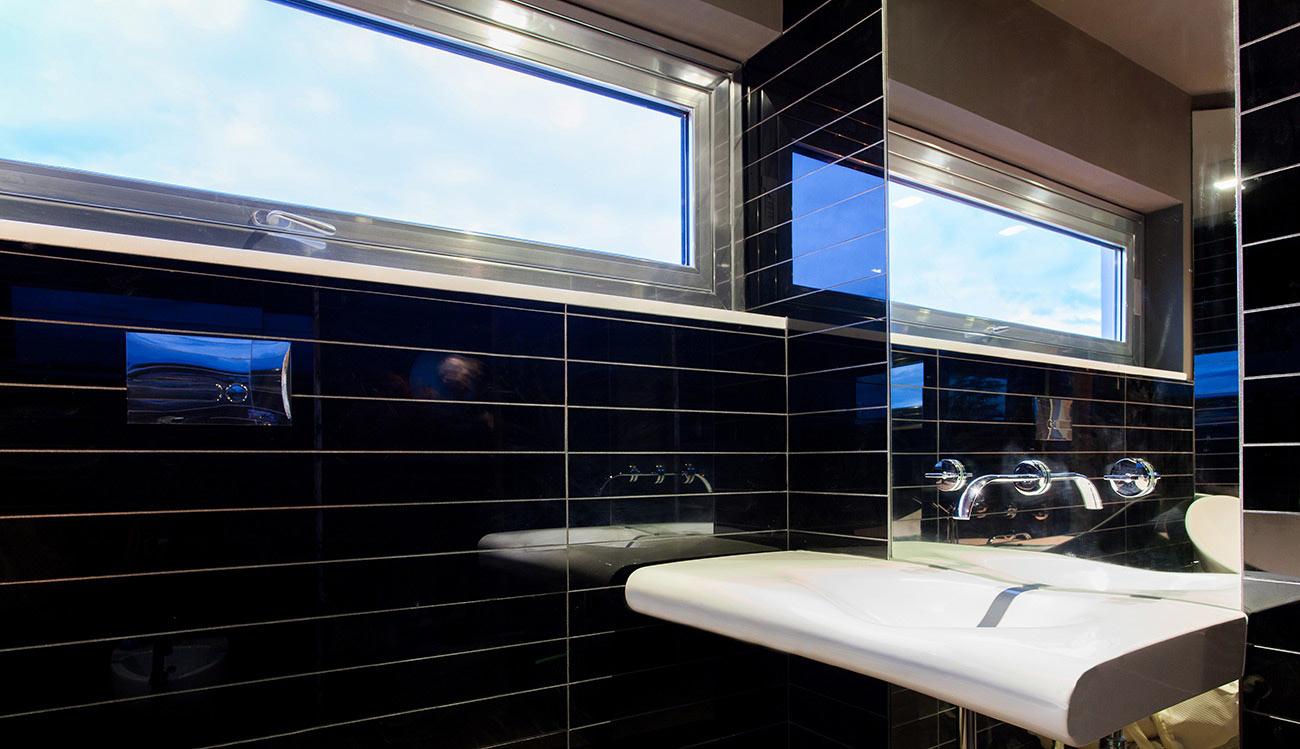 Lavabo a fianco di una parete con piastrelle nere e una piccola finestra