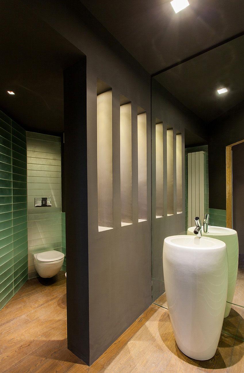 Bagno con una parete nera che divide i sanitari dal lavabo