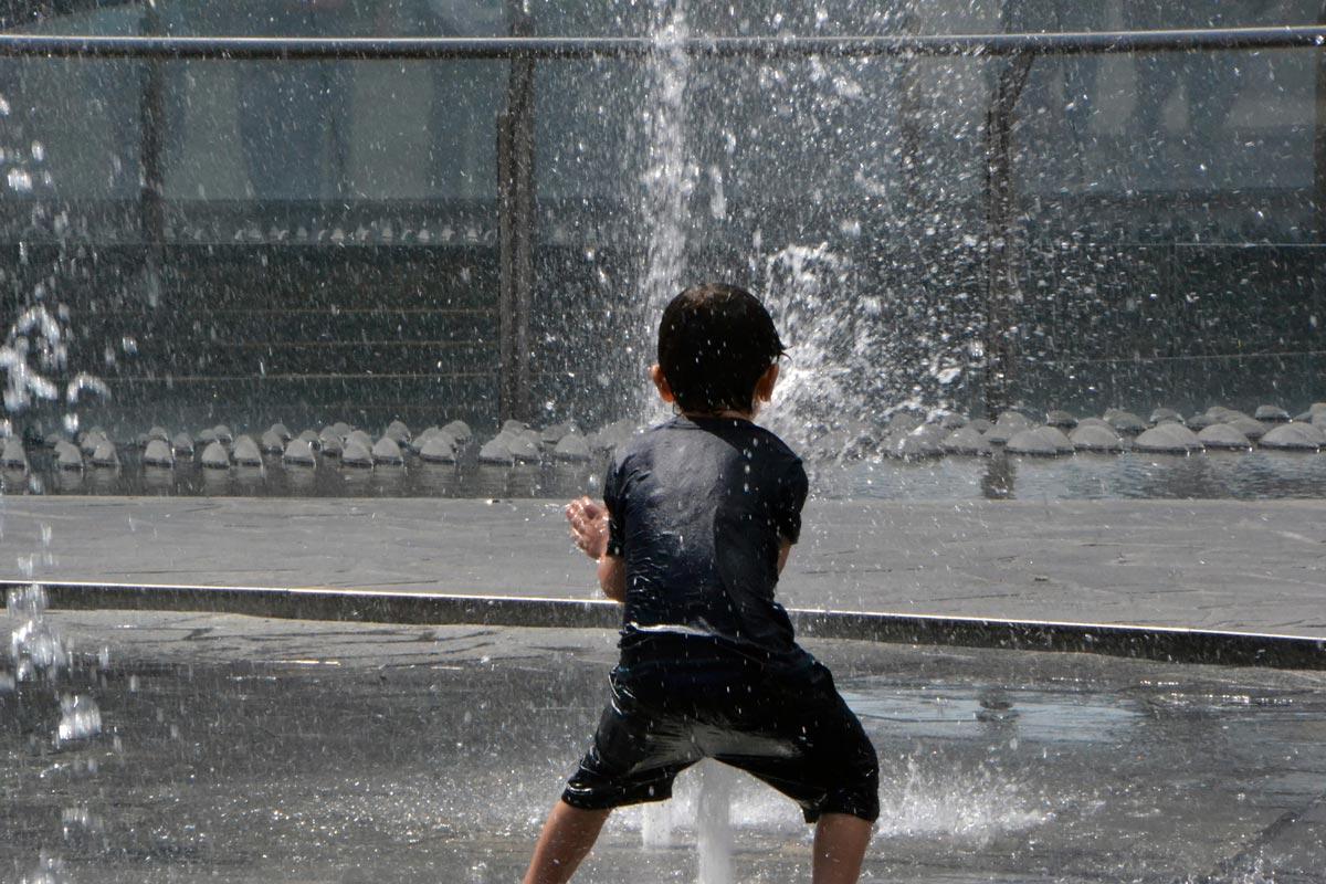 Bambino che gioca con una fontana