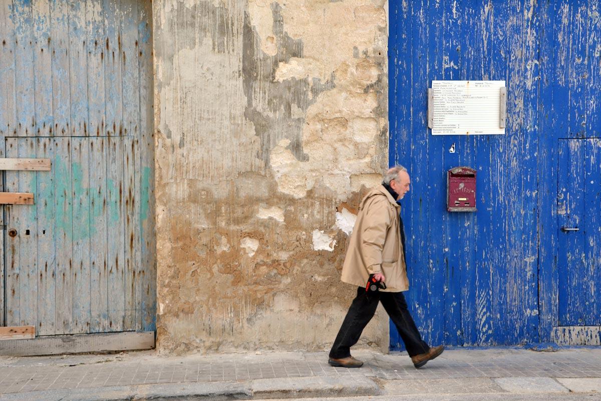 Anziano che passeggia lungo una via