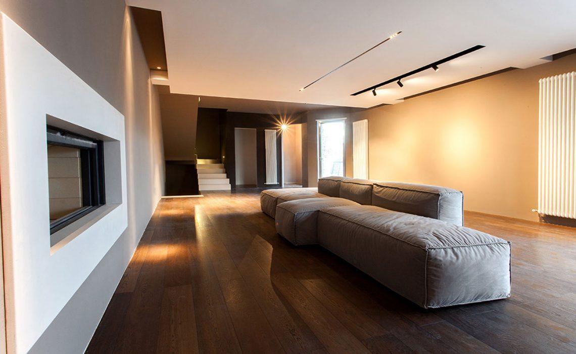 Soggiorno con pavimento in legno, un camino e un divano grigio al centro