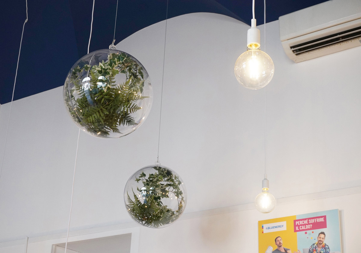 Sfere appese al soffitto che si armonizzano con i bulbi trasparenti dell'illuminazione