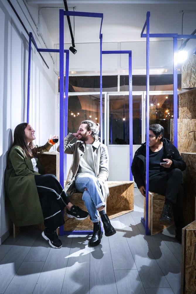 tre persone sedute su scatole di compensato fanno aperitivo