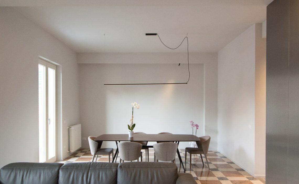 Foto del salotto con un divano e un tavolo con sopra orchidee