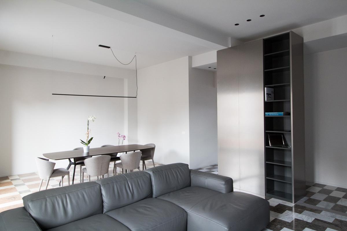 Salotto con divano grigio e tavolo. A lato una libreria