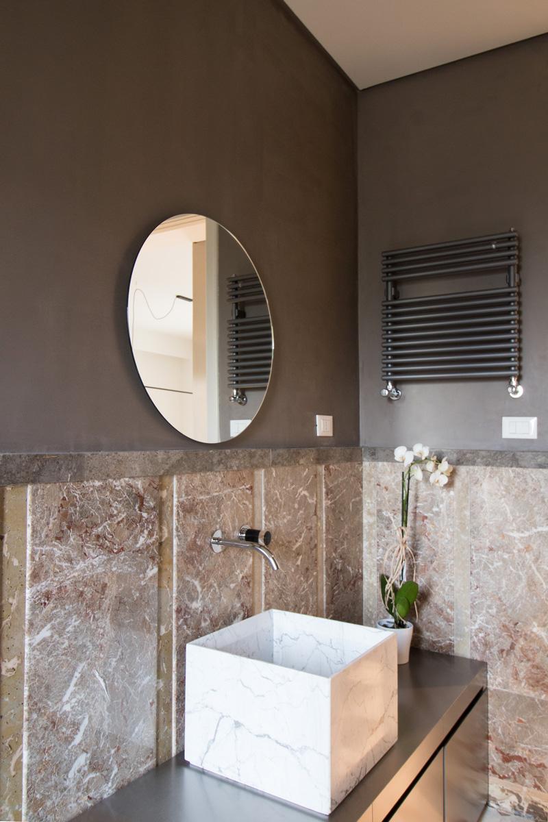 Bagno con specchio rotondo, lavabo in marmo e mobile in alluminio