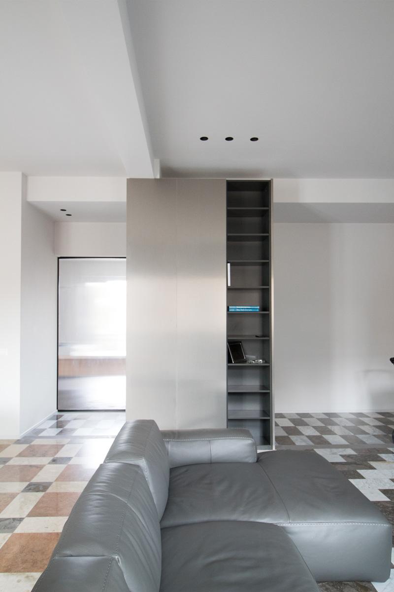 Stanza con piastrelle in marmo, divano grigio e libreria in alluminio