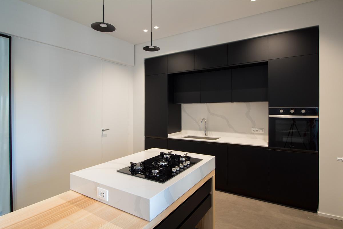 Cucina nera con isola bianca vista di lato