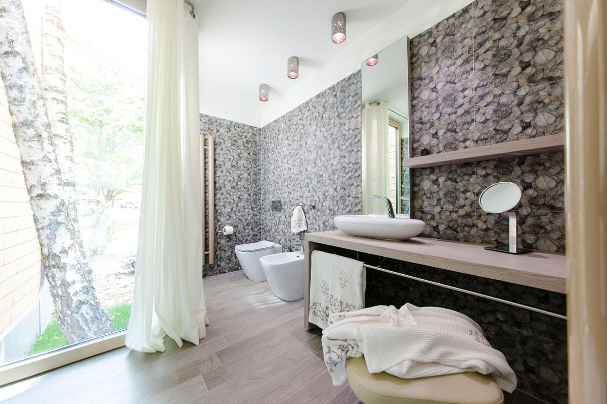 ampio bagno con vista sul giardino e muro decorato con foglie
