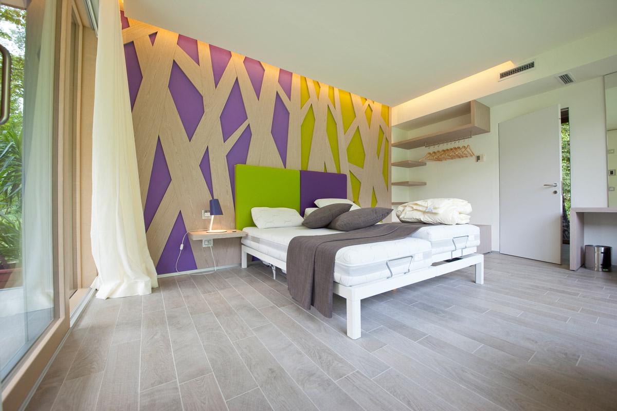 camera da letto matrimoniale con pareti decorate verdi e viola