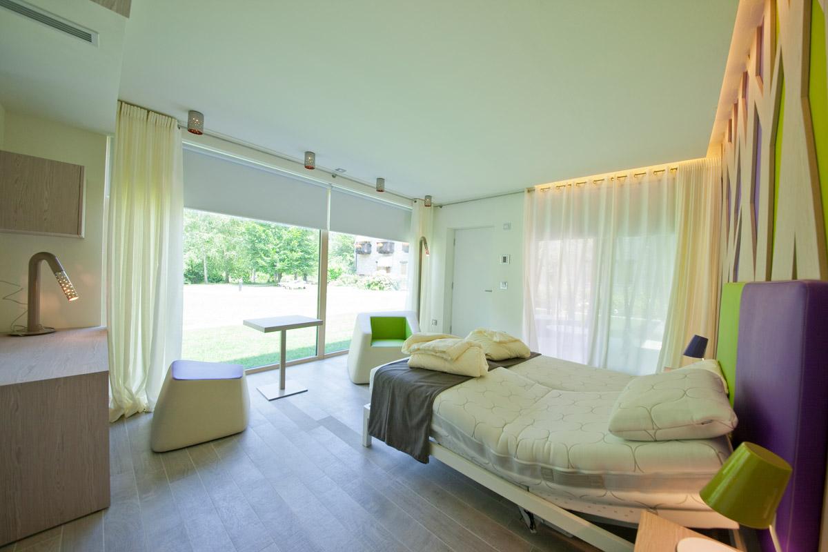 camera matrimoniale con ampie vetrate sul giardino