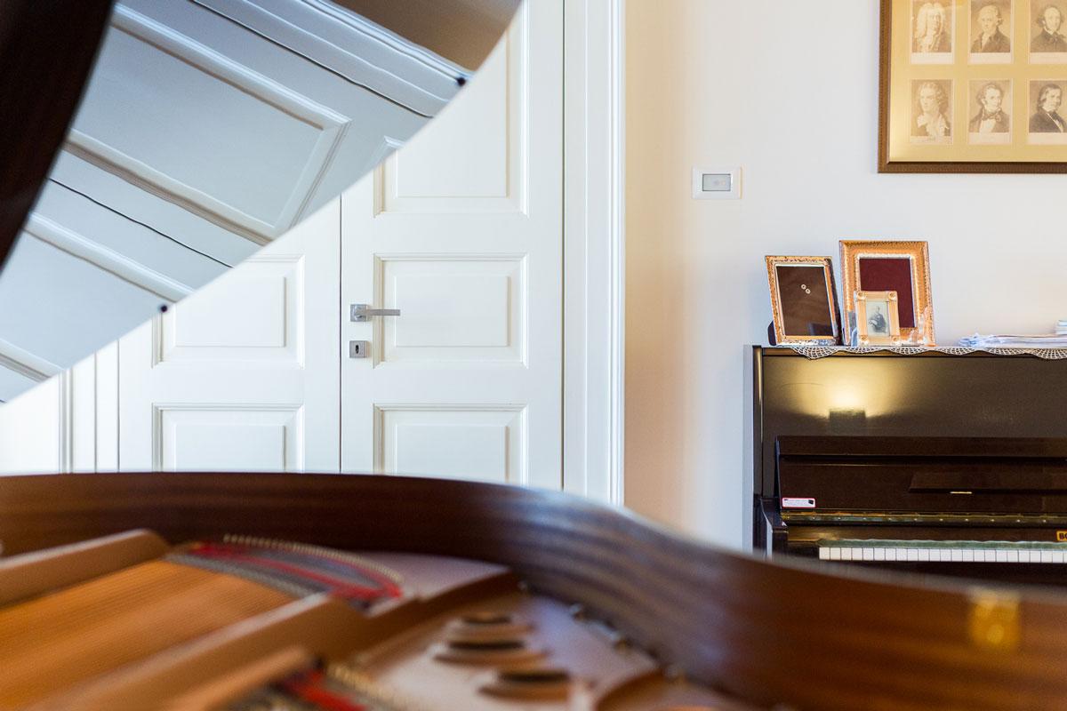pianoforte a coda nel salone e sullo sfondo la porta dello studio
