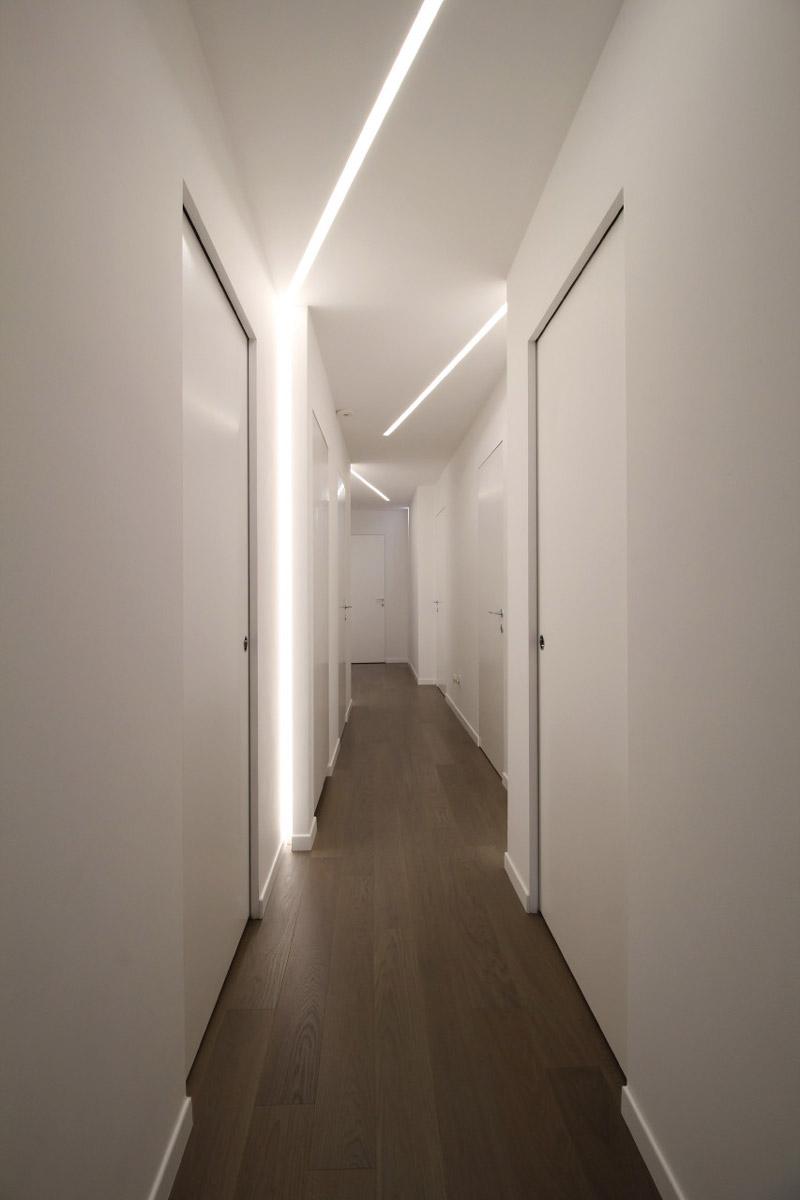 Lungo corridoio bianco con varie porte ai lati di colore bianco e un pavimento in legno