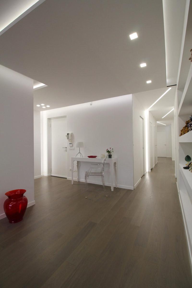 Lungo corridoio con una pavimentazione in legno e un tavolo bianco appoggiato sulla parete in angolo