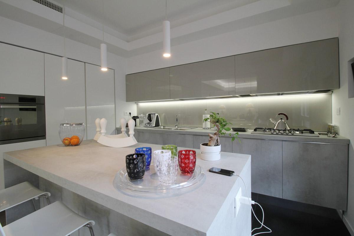 Bianca isola di una cucina con dei bicchieri e un bonsai appoggiati sopra